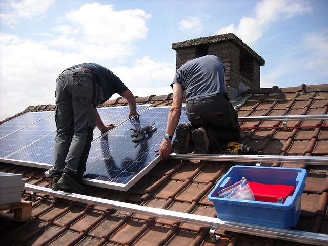 Two men workers providing solar panel financing